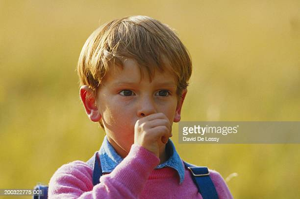 Boy (4-5) with thumb in mouth, looking away