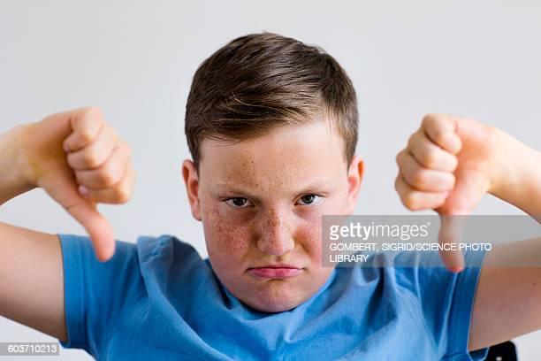 boy with thumbs down - sigrid gombert stock-fotos und bilder