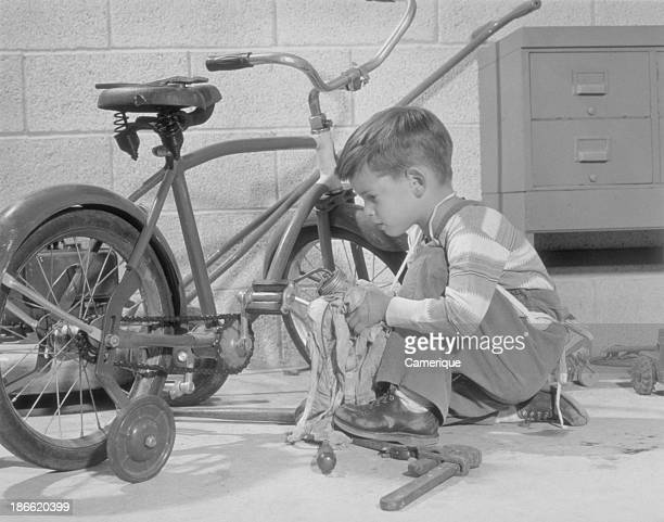 Boy with tools working on his bicycle Philadelphia PA 1958
