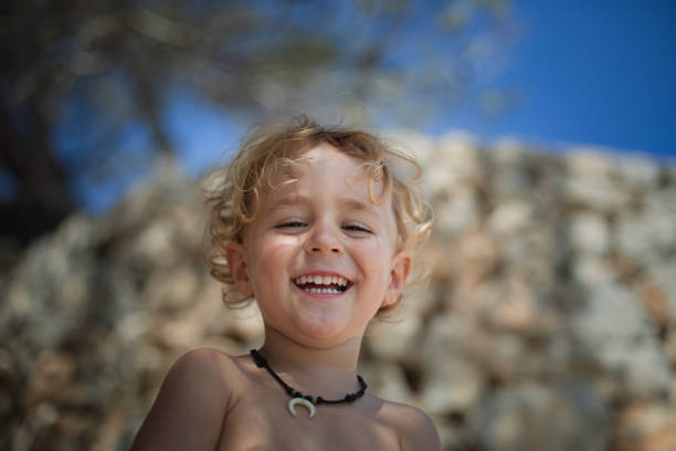 Boy with toothy smile in front of a stone wall at the beach