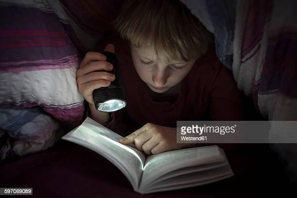 Boy with torch reading book under a blanket