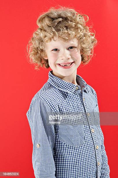 A boy with tousled curly blond hair smiling at the camera