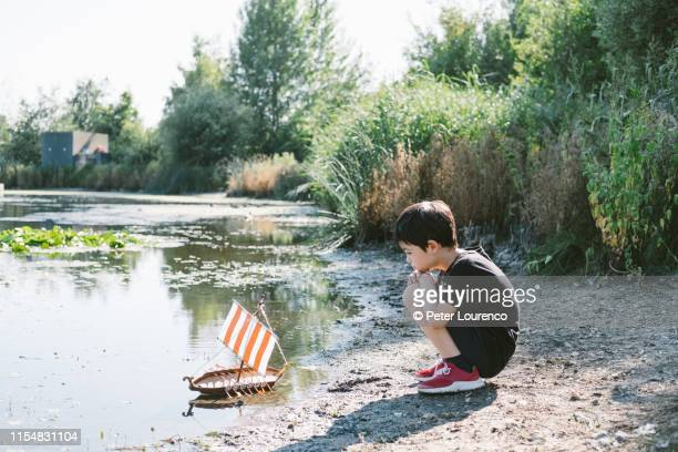 boy with toy boat at pond - peter lourenco ストックフォトと画像