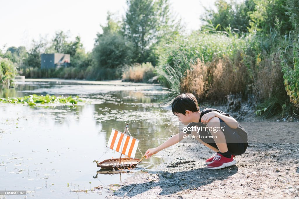 Boy with toy boat at pond : Stock Photo