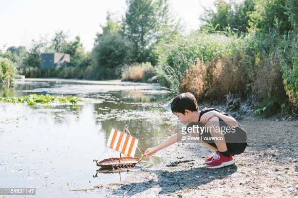 boy with toy boat at pond - riverbank stock pictures, royalty-free photos & images