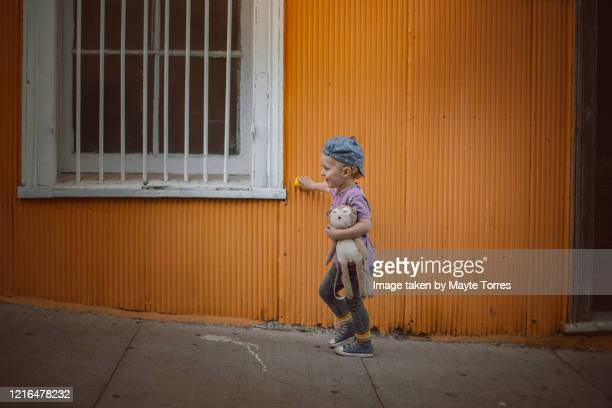 boy with toy car and teddy bear waling in a colorful street with car on the wall - valparaiso chile stock pictures, royalty-free photos & images