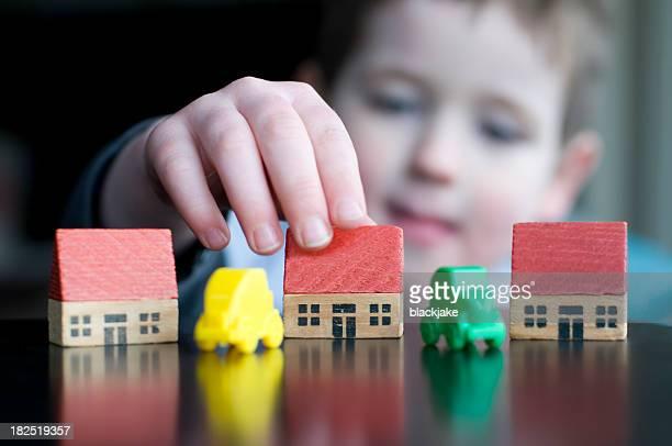 Junge mit Spielzeug-Häusern und Autos