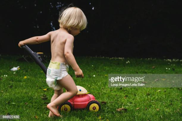 boy with toy lawnmower - diaper kids stock pictures, royalty-free photos & images