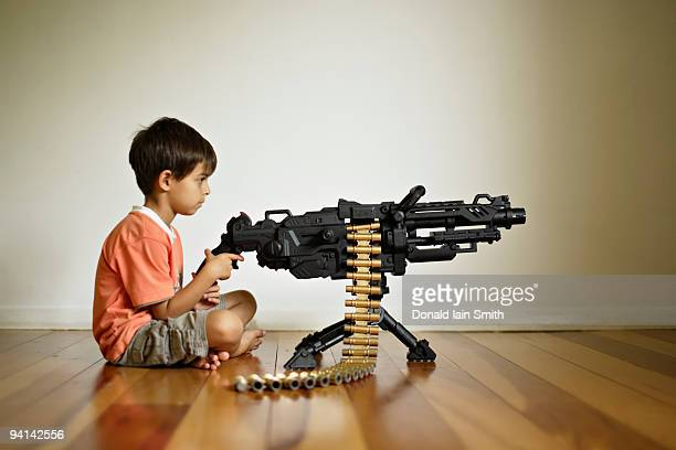 boy with toy machine gun - machine gun stock pictures, royalty-free photos & images