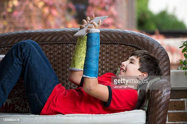 Boy with two broken arms enjoys time on a tablet.