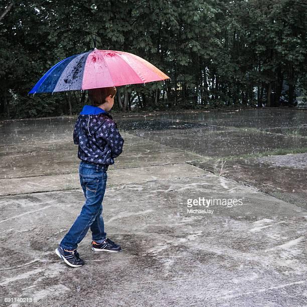Boy With Umbrella Walking On Street During Rainy Season