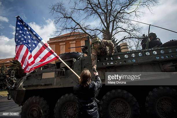A boy with US flag greets US soldiers of the 3rd Squadron 2nd Cavalry Regiment of the US Army as they arrive to Czech army barracks on March 30 2015...