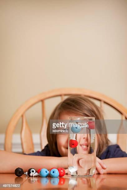 Niño con el agua de la molécula modelo flotante en vidrio