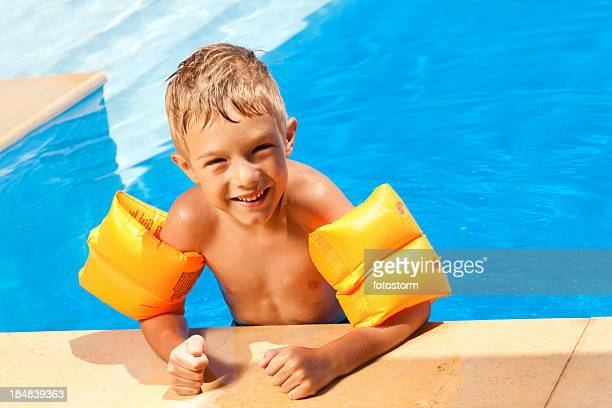 boy with water wings in the swimming pool - armband stock pictures, royalty-free photos & images