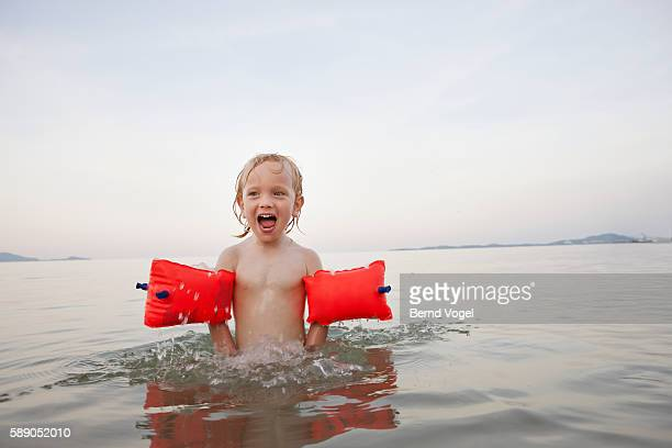 boy (7-9) with water wings swimming in lake - armband stock pictures, royalty-free photos & images