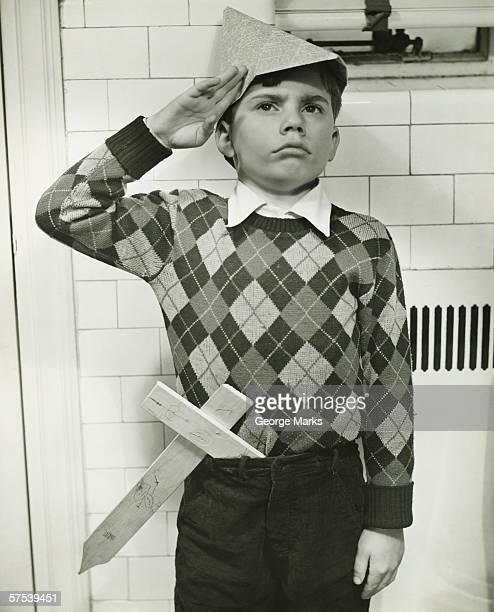 Boy (8-9) with wooden sword saluting indoors, (B&W)