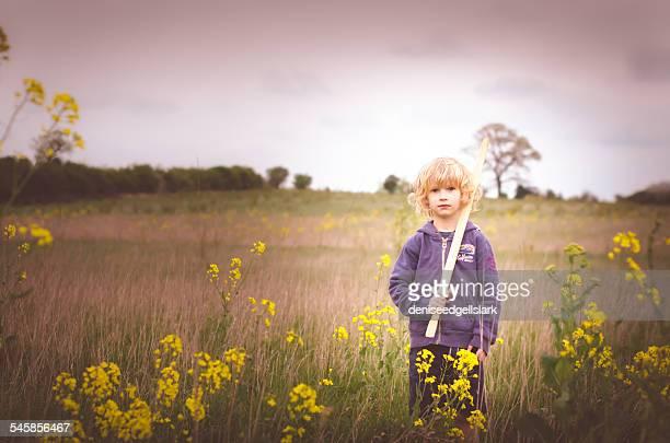 Boy with wooden sword standing in field