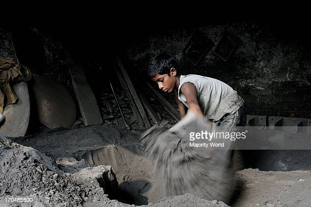 A boy working in a metal casting factory in Dhaka These factories employ young boys without any pay for the first year only providing them with two...