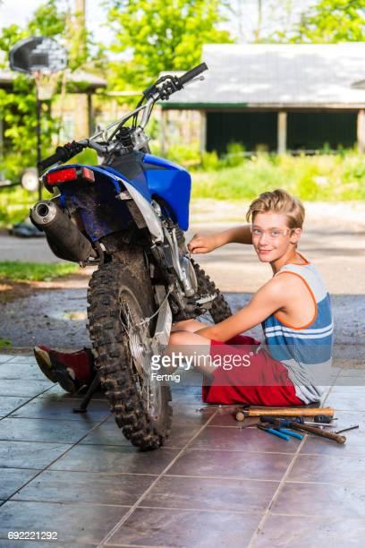 Boy working on a dirt bike