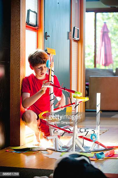 boy, 10, working on home-made paper roller coaster