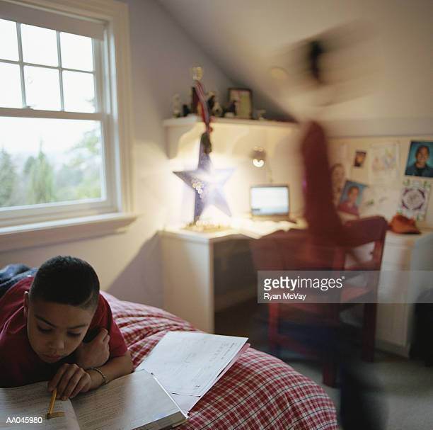 Boy Working on Homework, Brother Walking By