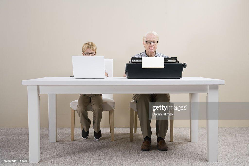 Boy (10-11) working on laptop and man working on typewriter sitting at table : Stock Photo