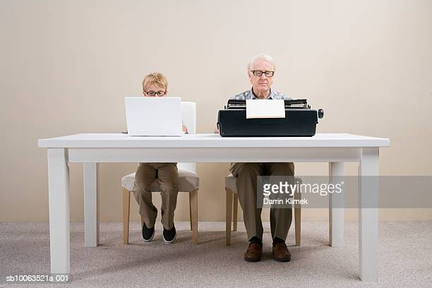 boy (10-11) working on laptop and man working on typewriter sitting at table - obsolete stock pictures, royalty-free photos & images