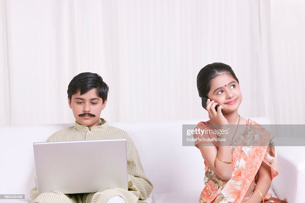 Boy working on laptop while girl talks on mobile phone : Stock Photo