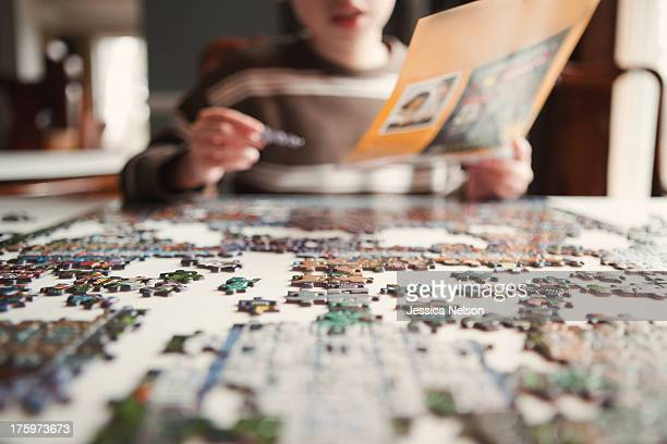 boy working on puzzle - raadsel stockfoto's en -beelden