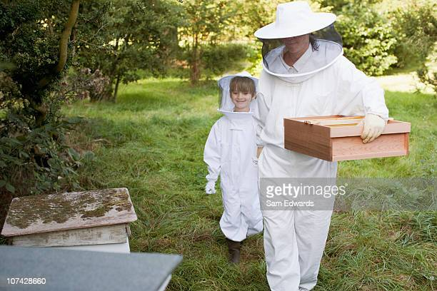 Boy working with beekeeper at beehive