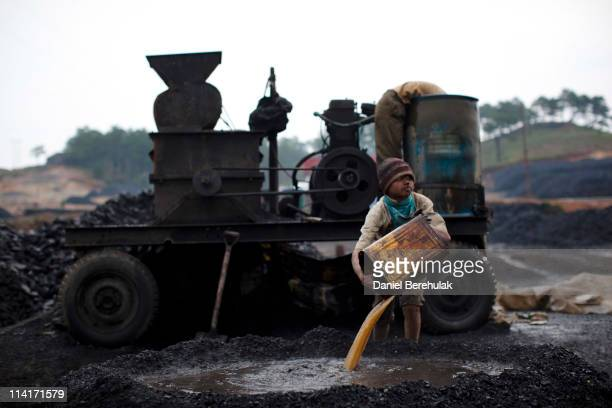 A boy works at a coal depot on April 16 2011 near to Lad Rymbai in the district of Jaintia Hills India Local schools in the area providing free...