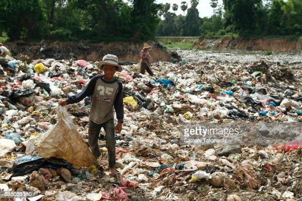 A boy works in a huge rubbish dump