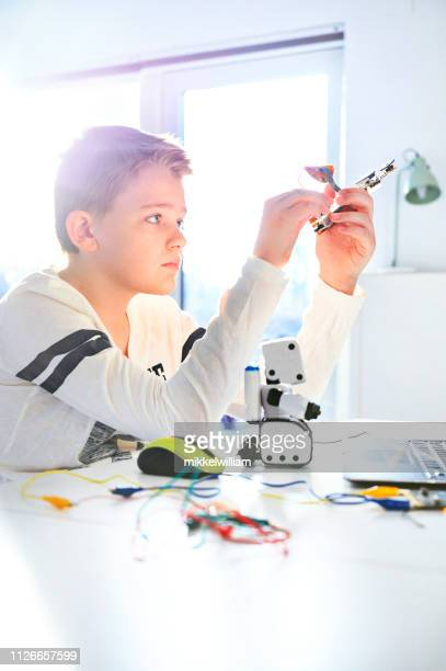 Boy works with a circuit board and a robot and tries to make new inventions