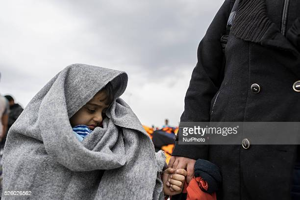 Boy wrapped in a cover stands in a harbour as migrants and refugees arrive on the Greek island of Lesbos while crossing the Aegean Sea from Turkey on...