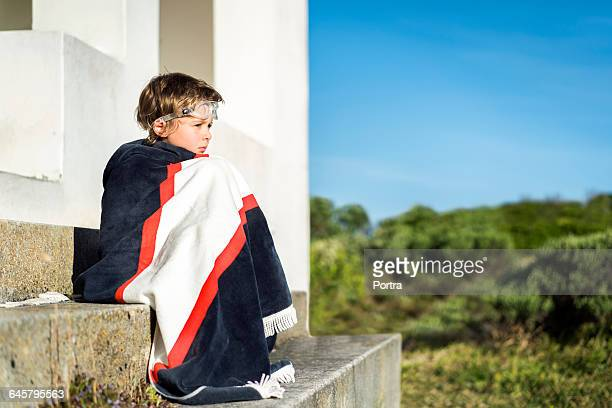 Boy wrapped in blanket while sitting on steps