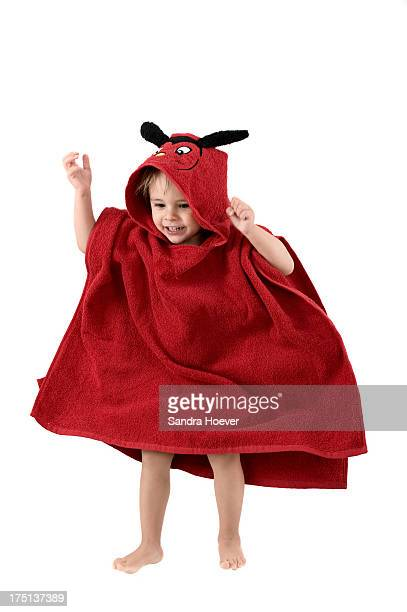 Boy (2-3) wrapped in towel jumping