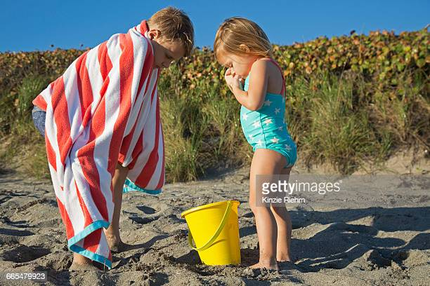 boy wrapped in towel looking down at toy bucket with sister on beach, blowing rocks preserve, jupiter island, florida, usa - jupiter island florida stock photos and pictures