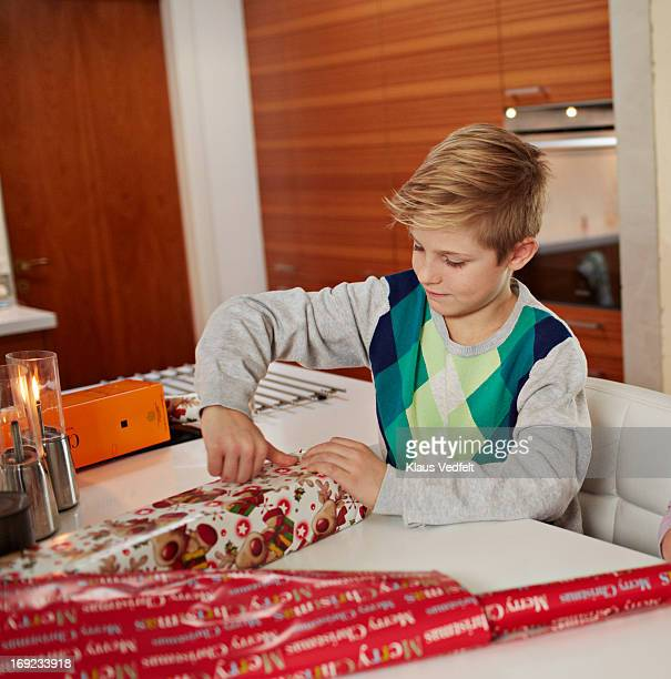 boy wrapping up christmas present - アーガイル模様 ストックフォトと画像