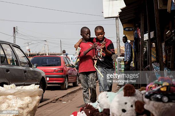 A boy wraps his arm around his friend as they walk down the street in Conakry Guinea on Wednesday January 21 2015