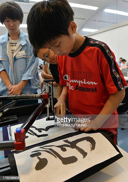 A boy writes a Chinese letter for study with a calligraphy robot which mimics the exact brush strokes of a master calligrapher at a science workshop...