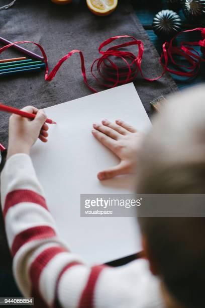 A boy writes a letter to Santa Calus