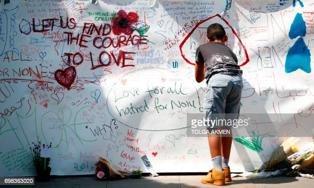 A boy writes a tributes near the scene of the June 19 van attack on pedestrians in the Finsbury Park area of north London on June 20 2017 Ten people...