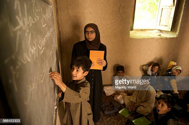 A boy writes on a blackboard at the Community Based School in a mosque in Qalae Haji Yahya village in Anjil district of Herat Province Afghanistan A...