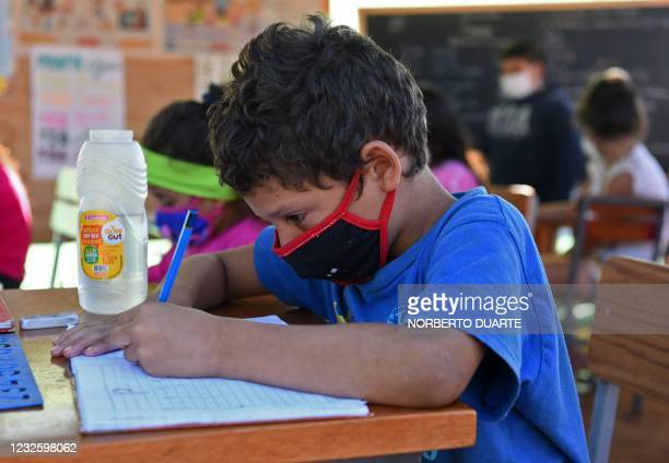 Boy writes on his notebook during a class at an open-air space in Asuncion, on April 29 amid the COVID-19 pandemic. - Since public schools are closed...