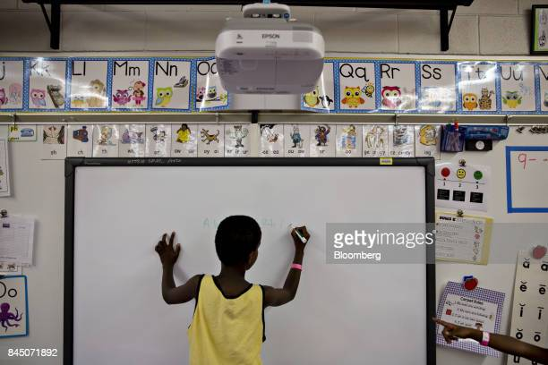 A boy writes the alphabet on a dryerase board in a classroom at Pizzo Elementary School an emergency shelter with over 1600 registered individuals in...