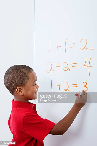 Boy writing answers to sums on whiteboard