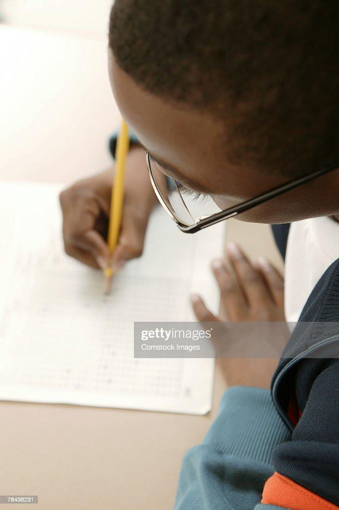 Boy writing at school : Stockfoto