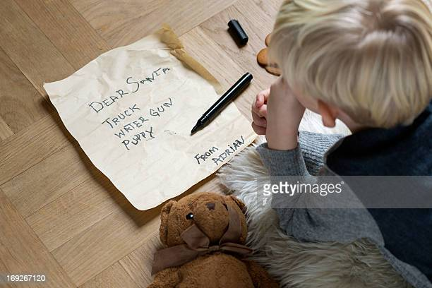 boy writing christmas list for santa - list stock pictures, royalty-free photos & images