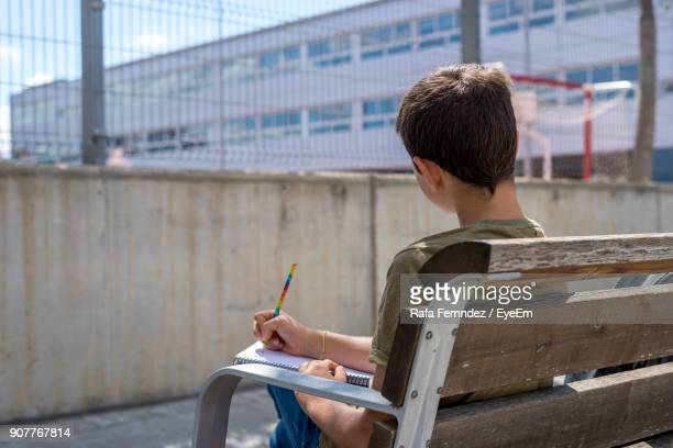Boy Writing In Book While Sitting On Bench