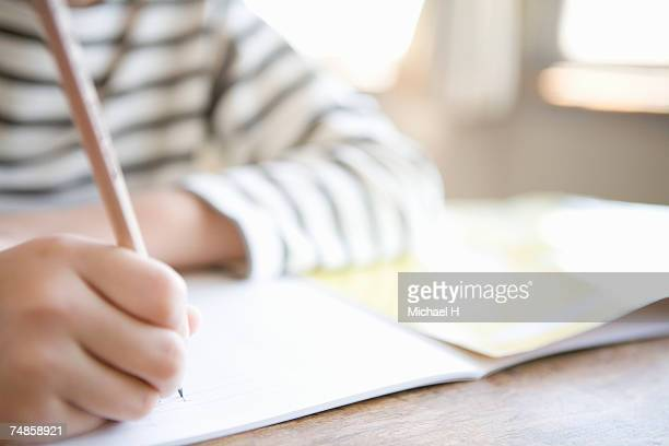 boy (8-9) writing in class, close-up - 教育 ストックフォトと画像